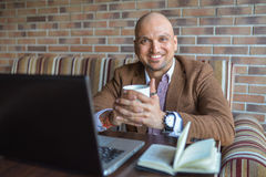 Happy Indian man sitting at cafe with notebook and laptop with cup of coffee, smiling looking at camera. Happy Indian man sitting at cafe with notebook and Royalty Free Stock Photo