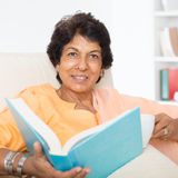 Happy Indian mature woman reading book. Portrait of a 50s Indian mature woman reading book and drinking coffee at home. Indoor senior people living lifestyle Royalty Free Stock Photography