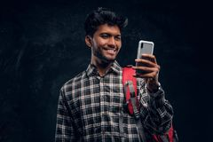 Happy Indian student with backpack chatting with his friends using a smartphone. Studio photo against a dark textured wall stock photography