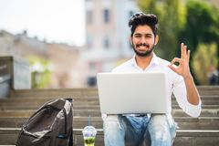 Happy indian student sitting on the stairs showing okay sign working on laptop, in the university campus. Technology, education an. Happy indian student sitting stock photography