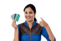 Happy Indian woman holding a bunch of debit cards-Cashless purch. Ase concept against white background Royalty Free Stock Photo