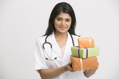 Happy Indian young doctor with gift boxes Stock Image