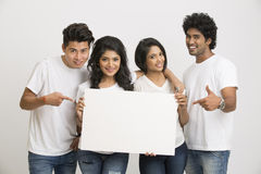 Happy Indian young people holding blank white board Stock Photography