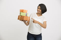 Happy Indian young woman pointing with her gift Royalty Free Stock Photos