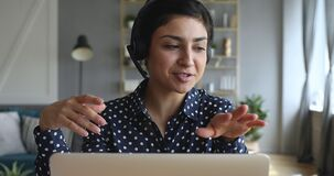 Happy indian young woman wear headset communicating by conference call