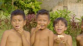 Happy indigenous children are enjoying eating sugarcane