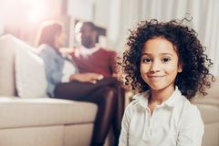 Glad child looking at camera while parents are sitting on sofa Royalty Free Stock Photo