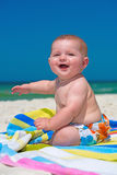 Happy infant baby boy sitting on towel at the beach Stock Photos