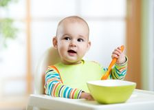 Happy cute infant baby boy spoon eats itself. Happy infant baby boy spoon eats itself Royalty Free Stock Photography