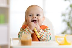 Happy infant baby boy spoon eats itself. At home royalty free stock images