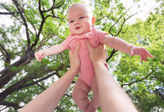 Happy infant baby girl being held up in the air royalty free stock photography