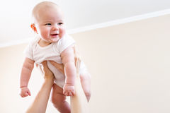 Happy infant baby girl being held up in the air. By her parent Stock Images