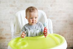 Happy infant baby girl with spoon eats itself at home in sunny kitchen . nutrition food for kids.  royalty free stock image