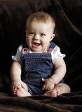 Happy infant baby laughing. Happy little baby girl dressed in jeans laughing Stock Photos