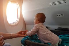 Happy infant baby lyes in special bassinet in airplane at his stomach. First flight of the baby, she is impressed and looking in. The window of plane stock photography