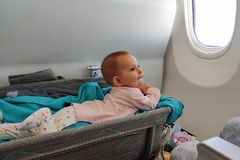 Happy infant baby lyes in special bassinet in airplane at his stomach. First flight of the baby, she is impressed but teething.  royalty free stock photography