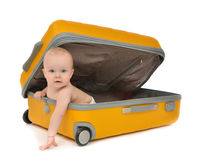 Happy infant baby toddler sitting in yellow plastic travel suitc Stock Photography