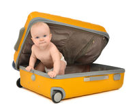 Happy infant baby toddler sitting in yellow plastic travel suitc. Ase on wheels getting ready for vacation and looking at the corner isolated on a white Stock Image