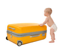 Happy infant baby toddler sitting in yellow plastic travel suitc. Ase on wheels getting ready for vacation and looking at the corner isolated on a white Royalty Free Stock Photography