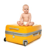 Happy infant baby toddler sitting in yellow plastic travel suitc Royalty Free Stock Image