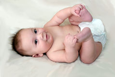 Happy Infant boy finds his toes Stock Photos