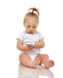 Happy infant child baby boy sitting smiling playing texting Stock Image