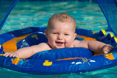 Happy infant playing in pool while sitting in baby float stock images