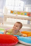 Happy infant on playmat. Happy cute infant lying on playmat, trying to crawl Royalty Free Stock Images