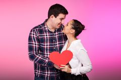 Happy couple with a heart in hand on pink background Stock Images