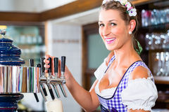 Happy Innkeeper in Bavarian pub drawing beer Royalty Free Stock Photos