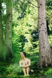 Happy innocent woman sitting in green atmospheric forest on background of  mountains in summer. Happy innocent woman sitting in green atmospheric forest on Stock Photography