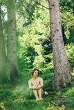 Happy innocent woman sitting in green atmospheric forest on background of  mountains in summer. Happy innocent woman sitting in green atmospheric forest on Royalty Free Stock Images
