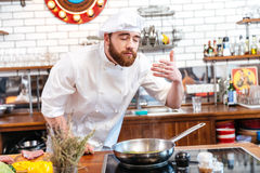 Happy inspired chef cook cooking and smelling aromas of food. Happy inspired bearded chef cook cooking and smelling aromas of food on the kitchen Royalty Free Stock Photos