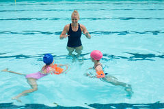 Happy instructor assisting children in swimming pool. High angle view of happy instructor assisting children in swimming pool stock photos