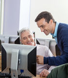 Happy Instructor Assisting Senior Man At Computer Desk Stock Image