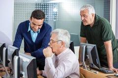 Happy Instructor Explaining Senior Men In Computer Class. Happy young male instructor explaining senior men in computer class Stock Photos