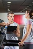 Happy Instructor Looking At Client Exercising On Stock Photography