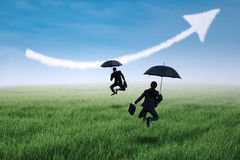 Happy insurance agent jumping with umbrella. And arrow up on the meadow Royalty Free Stock Photos