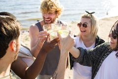 Lemonade cheers. Happy intercultural friends toasting with lemonade on weekend at seaside Royalty Free Stock Photography