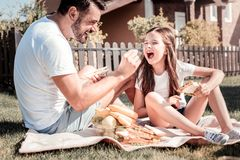 Happy interested father sitting and feeding his daughter. Its delicious. Happy interested unshaken father sitting on the ground holding a sandwich and feeding Royalty Free Stock Images