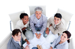 Happy international architects studying blueprints Stock Photos