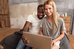 Happy international couple making online purchase at home. Enjoying online purchase. Smiling young international couple sitting at home and using laptop while Stock Photos