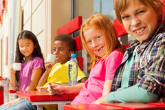 Happy international kids sit in outside cafe Stock Photos
