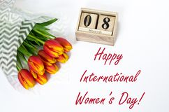 Happy International Women`s Day. Composition of bouquet of red tulip flowers and wooden cubs calendar, top view. Best greetings, royalty free stock image