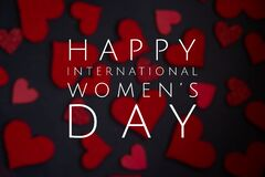 Happy International Women`s Day lettering with white text on black background with red heart