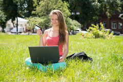Happy internet shopping woman online with laptop and credit card sitting outdoor on green grass. Internet shopper buying things on Stock Image