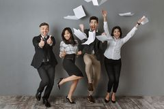 Happy interracial business people standing at grey wall after successful. Job interview stock photography