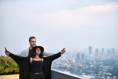 Lovely interracial couple on balcony. Happy interracial couple on the balcony on the background of the cityscape. Black girl wears dark clothes and a crimson hat Royalty Free Stock Photography