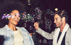 Happy interracial couple in a celebration with bubbles Stock Photo