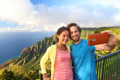 Happy interracial couple - hawaii travel selfie. Happy interracial travel couple taking selfie mobile phone picture at kalalau, lookout on na pali coast stock image